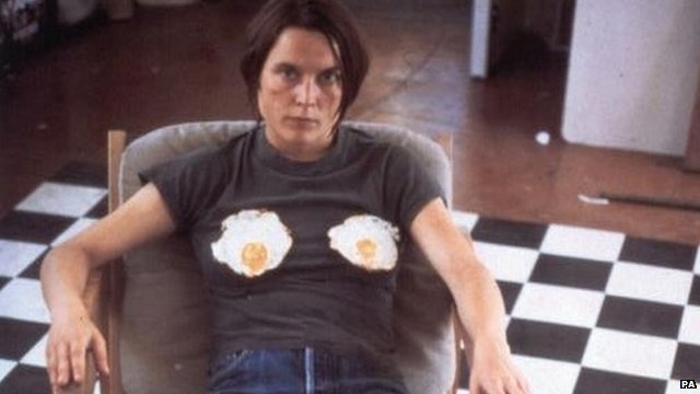 Sarah Lucas sitting with two fried eggs on her chest