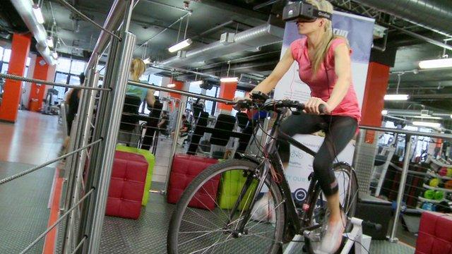 BBC Click's Lara Lewington rides a bicycle wearing a virtual reality headset