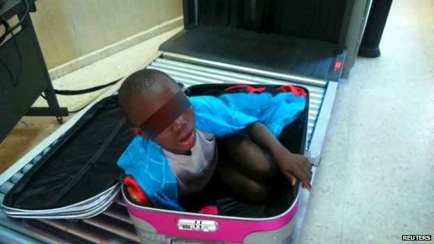 An eight-year-old boy is seen cramped inside a suitcase on a Spanish civil guard border security checkpoint between Morocco and Spain's North African enclave of Ceuta in this handout photo released May 8, 2015.
