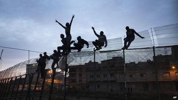 Sub-Saharan migrants climb over a metallic fence that divides Morocco and the Spanish enclave of Melilla. March 28, 2014