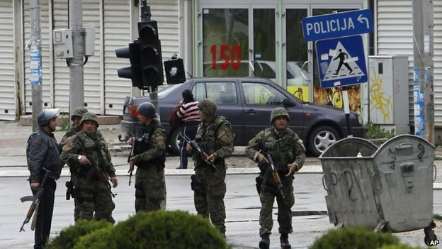 Police officers walk through a street near the scene of an altercation involving the police, in northern Macedonian town of Kumanovo, on Saturday, 9 May 2015