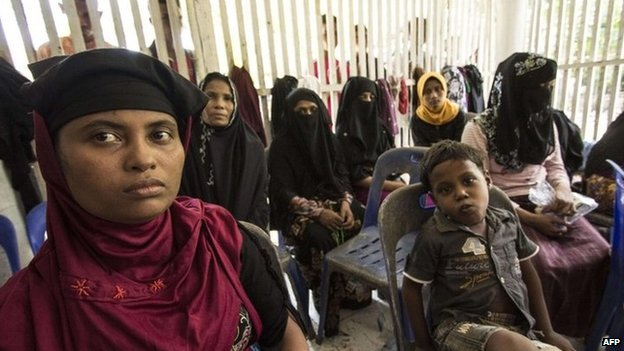 Migrant women and children from Myanmar and Bangladesh wait at a shelter after being rescued off Indonesian on 10 May