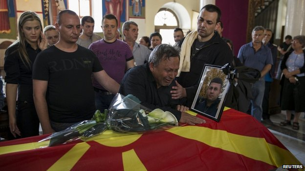 Relatives of killed policeman Sasho Samoilovski mourn next to his coffin covered in Macedonian flag inside a church in town of Tetovo, Macedonia, on 10 May 2015.