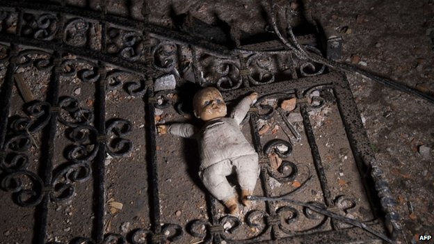 A doll on the ground at the entrance to a destroyed house following clashes between Macedonian police and an armed group in Kumanovo on 10 May 2015