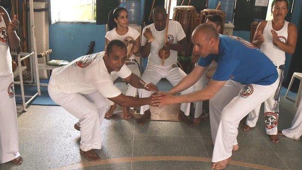 Doedd dim angen pâr da o 'sgidiau ar Jason i fynd i'r afael â 'capoeira' ar ei deithiau gyda'r BBC yn Brasil