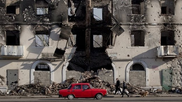 People pass by a destroyed building in Vuhlehirsk, Ukraine, 9 March 2015