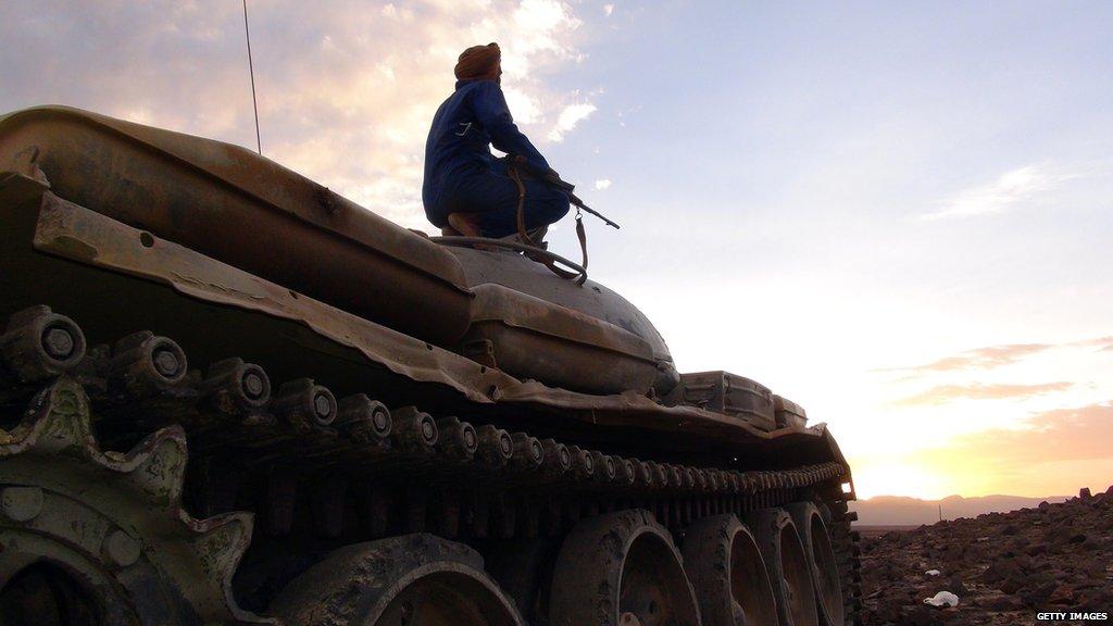 An armed Yemeni tribesman sits on a tank.