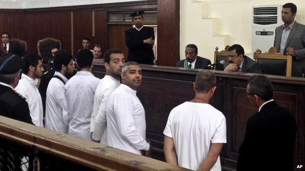 Baher Mohamed, Mohamed Fahmy and Peter Greste stand in front of a judge in Cairo (31 March 2014)