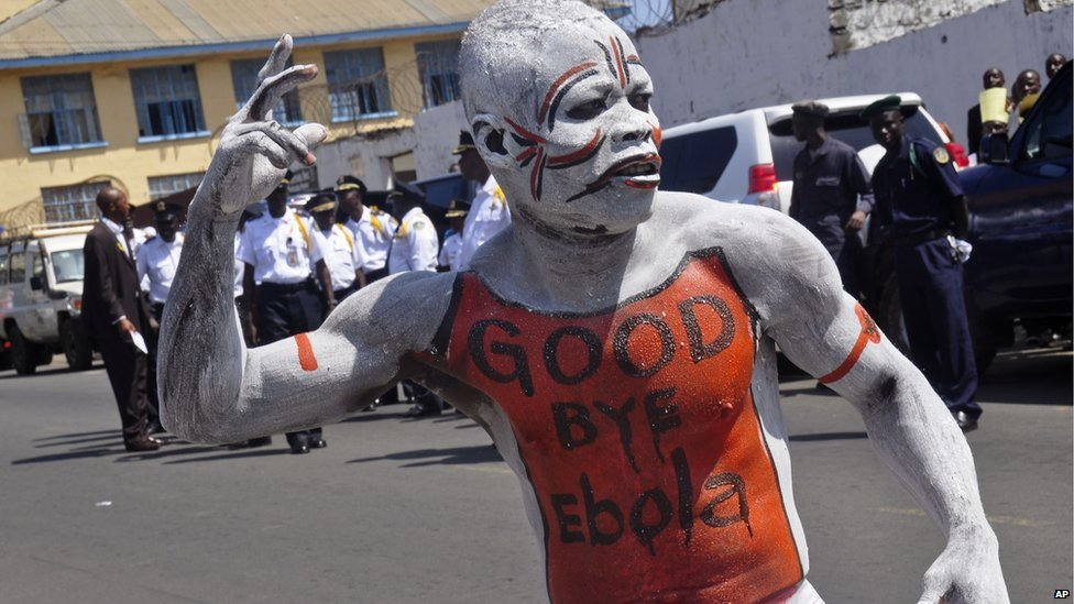 """A man dances in body paint with the words """"Good Bye Ebola"""" on his chest"""