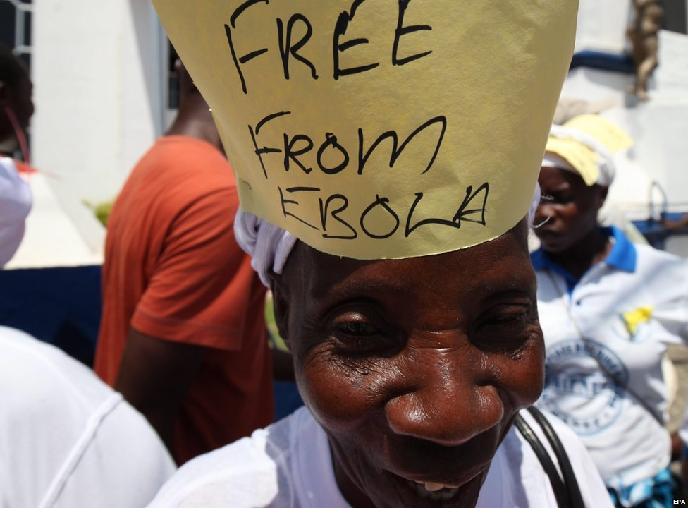 """A woman smiles with a sign saying """"Free from Ebola"""" on her head"""