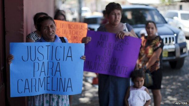 Women hold banners in support of Honduran domestic worker Carmelina Lopez Alvarado during a hearing in La Union on 16 April, 2015.