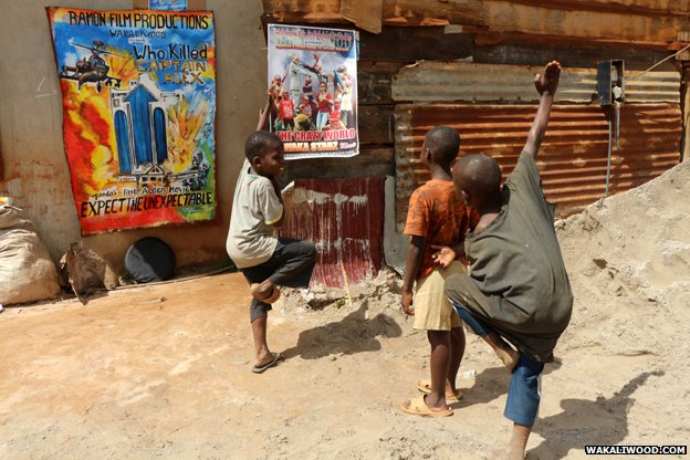 Children do kung fu poses in front of posters advertising the next Wakaliwood film