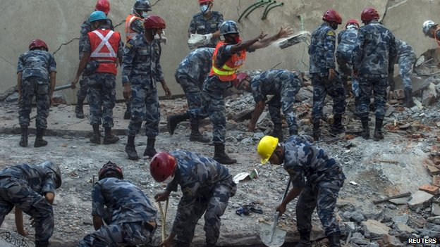 Rescuers work amid the latest quake damage in Kathmandu, 12 May