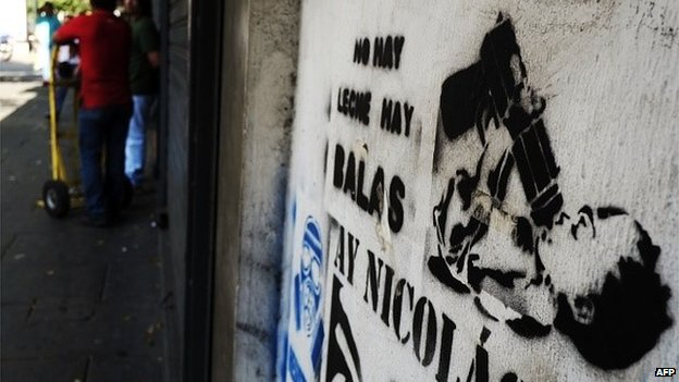 A stencil that reads 'There's no milk, there are bullets' on a wall in Caracas