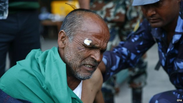 An injured man is treated at Kathmandu airport, 12 May