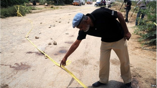 Pakistani security officials inspect the site