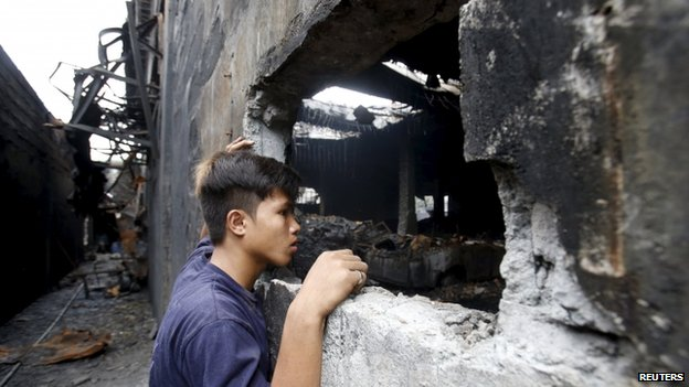 A worker who survived the fire look inside a gutted footwear factory in Valenzuela, Metro Manila in the Philippines on 14 May 2015. The