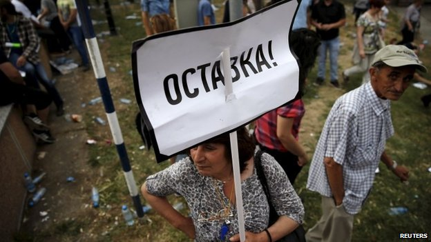 """A protester holds a sign that says """"resign"""" in Skopje on 17 May"""