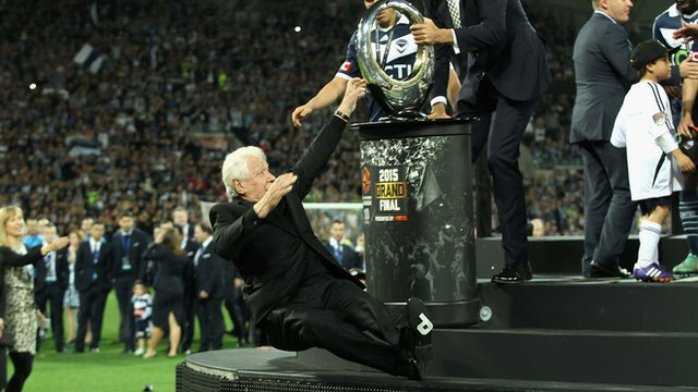 Football Federation of Australia chairman Frank Lowy avoids serious injury after falling off the stage as he was presenting the A-League trophy