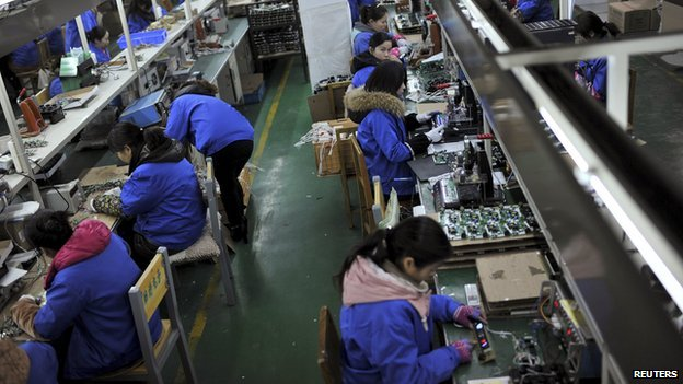 Employees assembling electronic components along a production line at a factory in Hefei, China