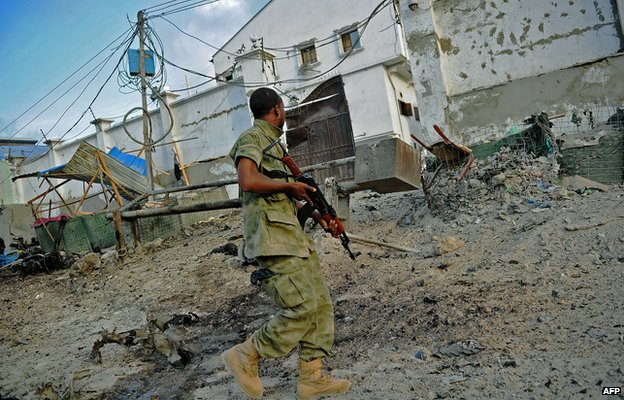 A solder walks past at the scene of a car bomb attack and armed raid by al-Shabab militants on the Maka al Mukarama hotel in Mogadishu 27 March 2015.