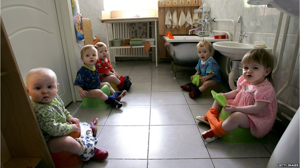 Children sitting on potties in an orphanage for HIV positive kids in Moscow