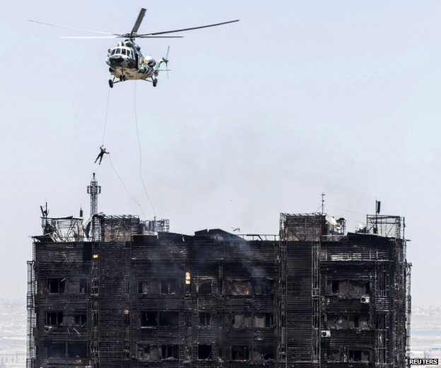 A rescuer descends from a helicopter over the roof of a burnt multi-storey residential building in Baku, Azerbaijan, 19 May 2015