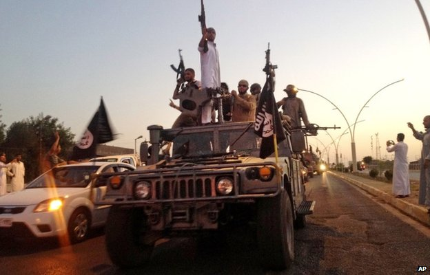 Islamic State militants drive through the Iraqi city of Mosul after its capture on 23 June 2014