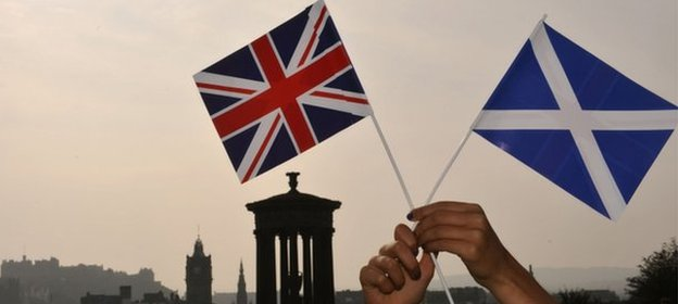 Saltire and Union Jack held up in front of the Edinburgh skyline