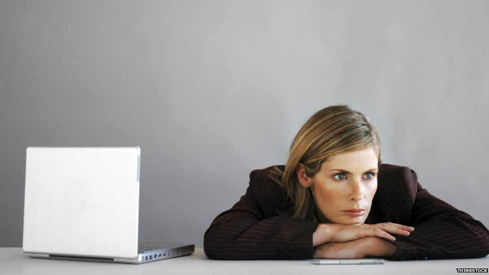 Woman at desk, looking bored