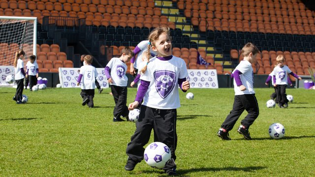a group of young children wearing Footy Pups t-shirts playing football on a field