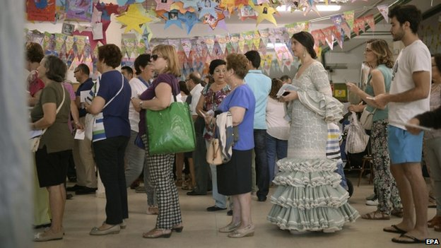 """Contrast in sartorial choices as locals queue to cast their vote in the crucial regional and local elections that are seen as a test of the conservative central government ahead of this autumn""""s general election at a pollling station in Cordoba, Spain, 24 May 2015"""