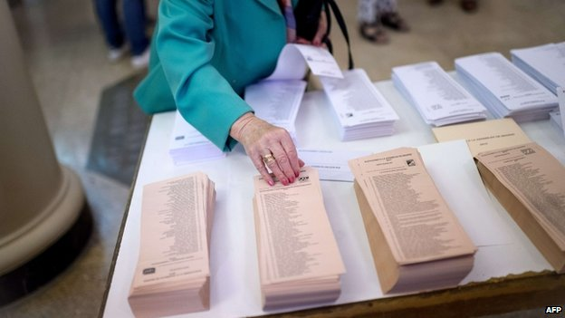 """A woman chooses her ballots in Spain""""s municipal and regional elections at a polling station in Madrid on May 24, 2015"""