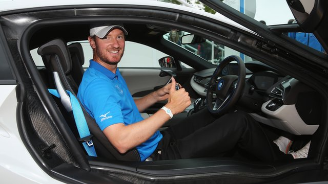 Golfer Chris Wood poses after winning a car for a hole-in-one at the PGA Championship at Wentworth