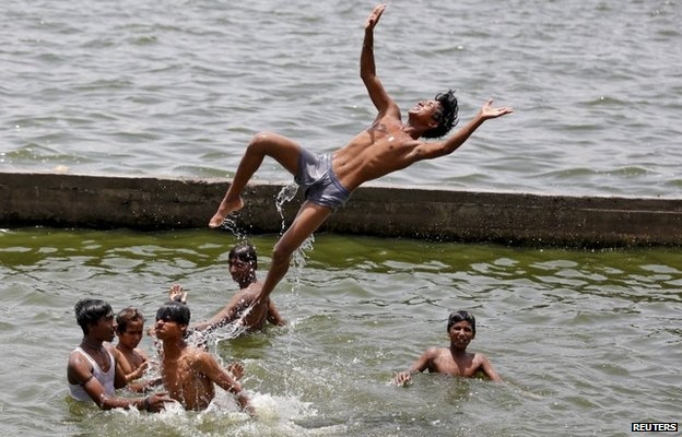 Boys cool off themselves in the waters of the river Sabarmati on a hot summer day in Ahmedabad, India, May 24, 2015.