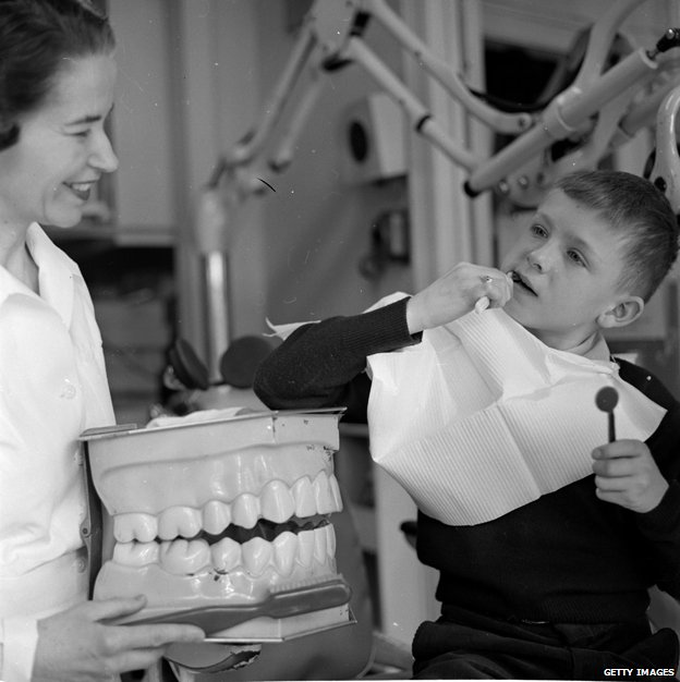 Dental nurse holding big fake teeth to teach young child how to brush