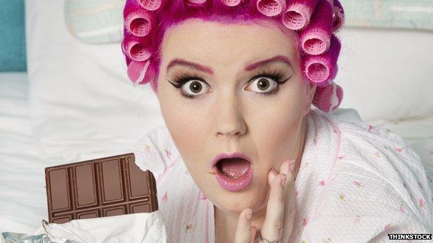 Surprised woman munching chocolate