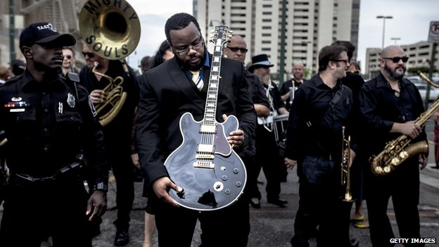 Rodd Bland, son of blues singer Bobby Bland, carries Lucille, one of BB King's beloved guitars.