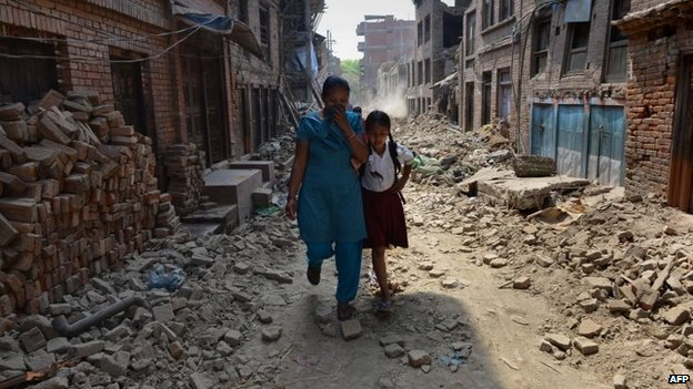 Schoolgirl Ankita Kapali, 11, walks with her mother past damaged buildings to school in Bhaktapur, near Kathmandu. Photo: 31 May 2015