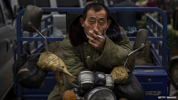 A Chinese labourer smokes a cigarette at a local market 26 September 2014