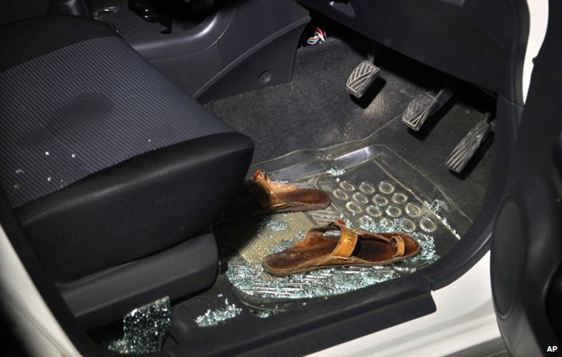 Sabeen's sandals in the footwell of her car, surrounded by shattered glass