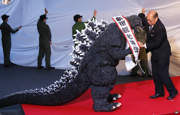 "Godzilla gets a sash of ""Shinjuku-ward tourism ambassador"" during its awards ceremony in Tokyo on Thursday, 9 April, 2015"
