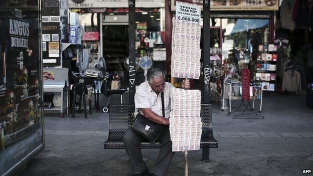 A lottery ticket seller rests at a bus-stop in Athens