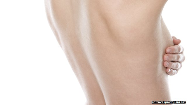 Close up of back of naked woman with her hand on right breast