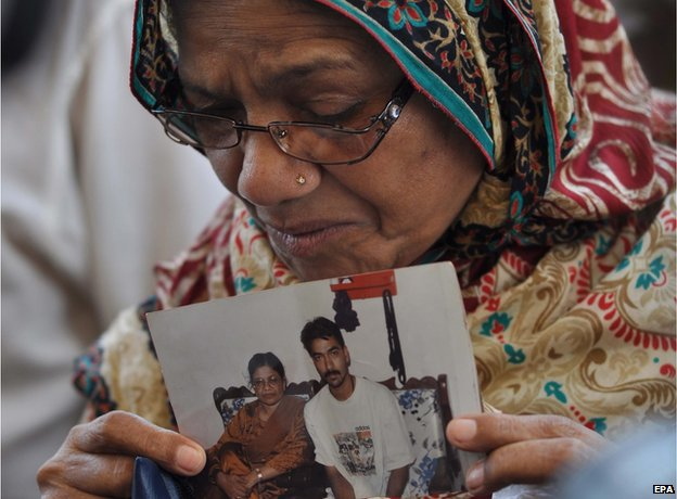 The mother of convicted activist Saulat Mirza, holds a portrait of her son after his body arrived for burial in Karachi on 12 May 2015