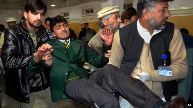 Pakistani volunteers carry a student injured in the shootout at a school under attack by Taliban gunmen