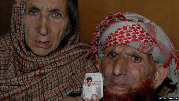 Kashmir parents of convicted killer Shafqat Hussain, displaying a photograph of their son, in Muzaffarabad,
