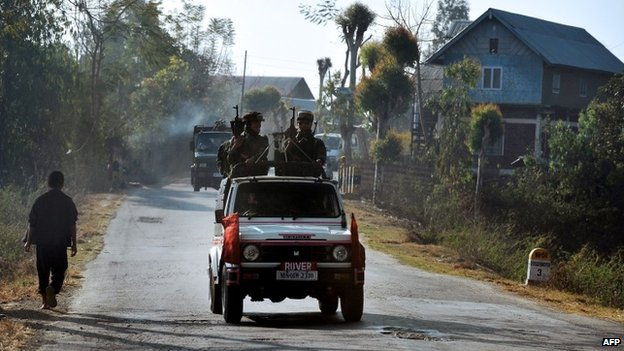 In this photograph taken on February 18, 2012, a vehicle carrying armed security personnel passes along a road on the outskirts of Imphal in the north eastern Indian state of Manipur.