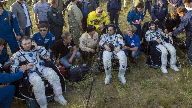 Nasa astronaut Terry Virts, Russian cosmonaut Anton Shkaplerov and European Space Agency astronaut Samantha Cristoforetti rest after landing
