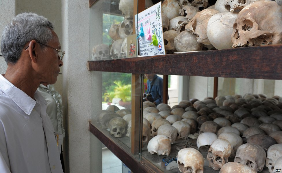 A visitor looks at skulls at Tuol Sleng